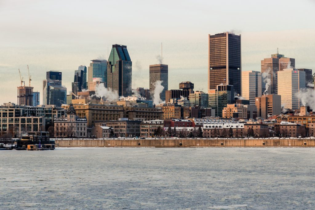Image of a cityscape of Montreal in the winter, taken from out in the water looking into the city