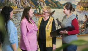 Yukon College President Karen Barnes stands chatting with three indigenous women