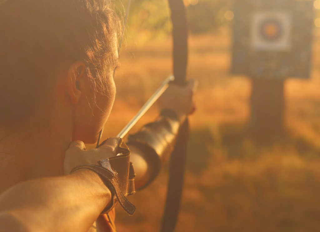 orange-hued image of a woman shooting a bow and arrow