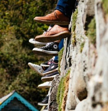 photo of feet of young people dangling over a ledge as they sit on a small cliff by the ocean