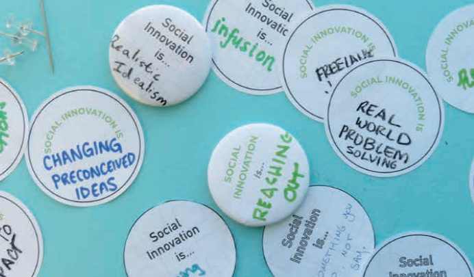 "Some stickers and buttons with different social innovation concepts written on them (""social innovation is: ...changing preconceived ideas""; ""social innovation is: real-world problem solving"")"