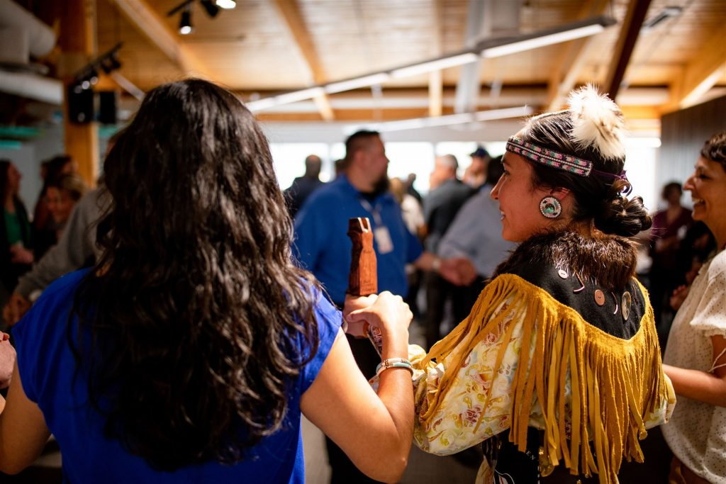 Two women holding hands during a traditional Indigenous round-dance